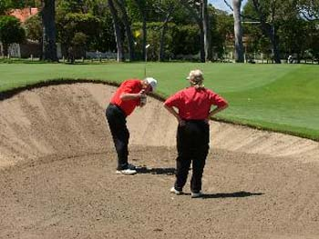 Photo of a Blind Golfer and Caddy, chipping out of a bunker